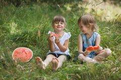 Two girls friends eating watermelon and having fun outdoor stock photography