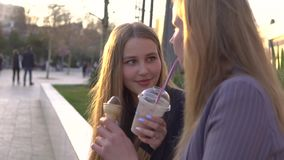 Two girls friends having fun on evening broadway. Eating ice cream and drinking ice fresh milk shake