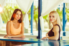 Two girls friends having fun outdoor in summer. Woman are waiting for their cocktails Stock Photography