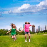 Two girls friends jumping happy holding hand in city skyline Stock Photos