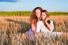 Two girls friends lean each another Royalty Free Stock Photos
