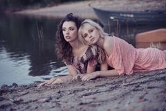 Two girls friends lying down at the beach Royalty Free Stock Image