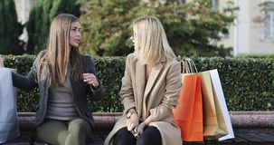 Two girls friends meet each other in city park after shopping. Brunette woman talks and shows a new scarf to friend. 4K stock footage