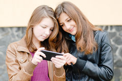 Two girls friends with mobile touch phone Royalty Free Stock Images