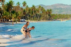 Two girls friends play and frolic on a tropical beach. The concept of female friendship Stock Photos