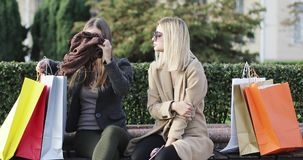 Two girls friends sit on bench in city park after shopping. Brunette woman talks and shows a new scarf to friend. 4K stock video footage