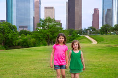 Two girls friends walking holding hand in urban skyline Stock Photo