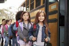 Two girls at the front of the elementary school bus queue royalty free stock photos