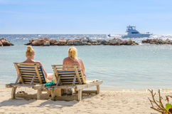 Two girls in a front row seats at the beach Stock Images