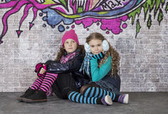 Two girls in front of the wall covered with graffiti Royalty Free Stock Images