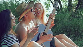 Two girls with funny boy resting on the grass and playing the guitar stock video footage
