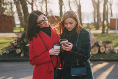 Two girls with gadget. Girls walking around town on a sunny day with phones sitting on a bench and drink coffee Stock Photography