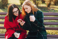 Two girls with gadget. Girls walking around town on a sunny day with phones sitting on a bench and drink coffee royalty free stock image