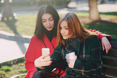 Two girls with gadget. Girls walking around town on a sunny day with phones sitting on a bench and drink coffee royalty free stock photo