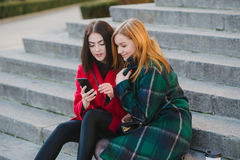 Two girls with gadget. Girls walking around town on a sunny day with phones sitting on a bench and drink coffee stock image
