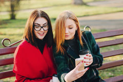 Two girls with gadget. Girls walking around town on a sunny day with phones sitting on a bench and drink coffee stock photo
