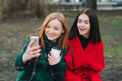Two girls with gadget. Girls walking around town on a sunny day with phones sitting on a bench and drink coffee stock images