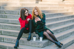 Two girls with gadget. Girls walking around town on a sunny day with phones sitting on a bench and drink coffee stock photos