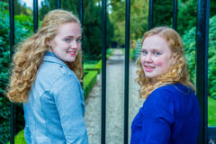 Two girls at gate of footpath in park Stock Photo