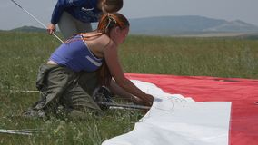 Two girls gather hang glider stock footage