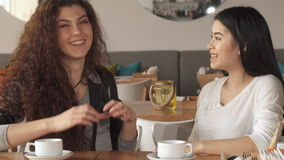 Two girls gesture hearts at the cafe. Two cute girls gesturing hearts at the cafe. Pretty young asian and caucasian women having fun together. Attractive couple stock footage