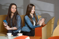 Isolate. Two girls getting lost in and separated by their mobile devices Royalty Free Stock Image