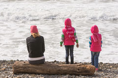 Two girls and a girl on beach sitting on a log and looking into the distance Royalty Free Stock Photos