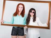 Two girls girlfriend got into the frame of the picture, optimistic lady having solution and bored, annoyed clueless sad Stock Images