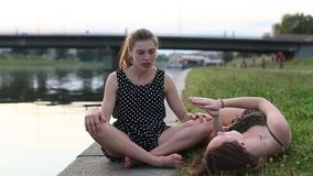 Two girls girlfriend sitting on the city waterfront and fun talk. Two young girls girlfriend sitting on the city waterfront and fun talk stock video footage