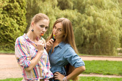 Two girls girlfriends eat lollipop Stock Photos