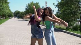 Two girls girlfriends are happy and fooled in the park in sunny weather. slow motion. Two beautiful girlfriends are happy and fooled in the park in sunny weather stock footage