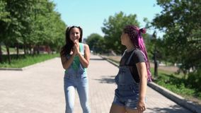 Two girls girlfriends are happy and jumping in the park in sunny weather. slow motion. Two beautiful girlfriends girlfriends with long hair are happy and jump in stock video footage