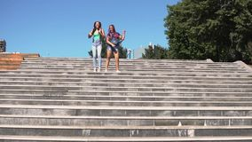 Two girls girlfriends are happy and jumping standing on the steps on the street. Two girls girlfriends are happy and jump standing on the steps on the street stock footage