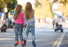 Two girls girlfriends rollerblading on the mall. Rear view Royalty Free Stock Image