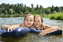 Two girls girlfriends on summer lake swimming in the lake and sm Royalty Free Stock Image