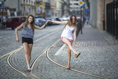 Two girls girlfriends walk along the tram tracks. Stock Photos