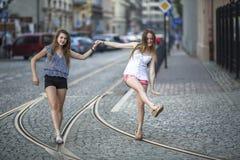 Two girls girlfriends walk along the tram tracks. Stock Photos