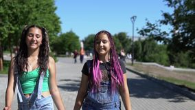 Two girls girlfriends are walking in the park having a good mood. slow motion. Two girlfriends girlfriends with long hair walk in the park having a good mood stock footage