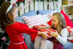 Two girls give Christmas gifts. Two girls give gifts near a Christmas tree in rabbit ears near the bed Stock Photography