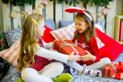 Two girls give Christmas gifts. Two girls give gifts near a Christmas tree in rabbit ears near the bed stock images