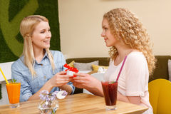 Two girls giving each other presents in cafe. Pleasant time. Two pretty smiling women sitting in cafe and giving each other little present Stock Photo