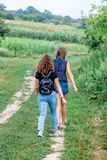 Two girls go on a dirt road. Summer trip in the countryside_ royalty free stock photo