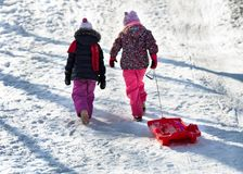 Two girls go uphill with sledges Royalty Free Stock Images