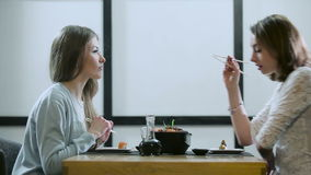 Two girls gossiping in a Japanese restaurant stock video footage