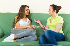 Two girls gossiping on sofa at home Royalty Free Stock Images