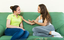 Two girls gossiping on sofa at home Royalty Free Stock Photos