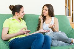 Two girls gossiping on sofa at home Royalty Free Stock Photography