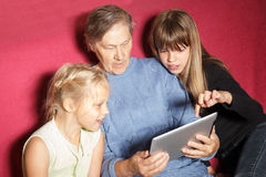 Two girls and grandmother using digital tablet Royalty Free Stock Image