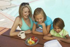 Two Girls (7-9) and Grandmother Watching portable television by swimming pool. Royalty Free Stock Images