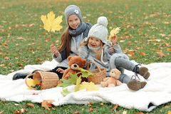 Two girls in a gray caps arrange a picnic in autumn park in the evening Stock Image